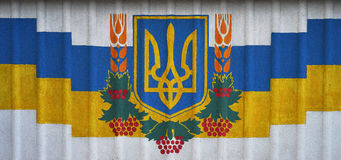 The national flag of Ukraine and the national emblem of independent Ukraine are trident painted on a white fence wall, street art, Stock Photos
