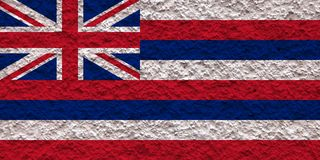 The national flag of the US state Hawaii in against a gray wall with stony surface on the day of independence in color of blue red stock photos