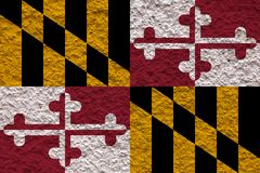 The national flag of the US state Maryland in against a gray wall with stony surface on the day of independence in black, red and royalty free stock image