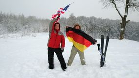 National flag of USA and Germany waving in the wind. With blurred mountains in the background. Two people hold the flags in a blizzard and a strong wind stock footage