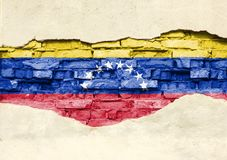 National flag of Venezuela on a brick background. Brick wall with partially destroyed plaster, background or texture royalty free stock images