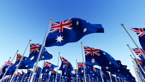 The National flags of Australia against blue sky. Royalty Free Stock Image