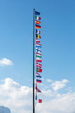 The National flags and the flag of the European Union flying in the wind in front of a blue sky Stock Image