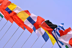 National flags in line. Different countries national flags getting together under blue sky, shown as worldwide, country, and international communication or Royalty Free Stock Images