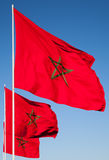 National flags of Morocco above blue sky Stock Photo