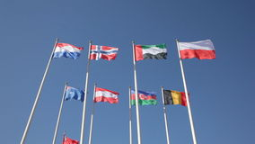National flags of various countries. Fluttering in the wind against a blue sky stock video footage