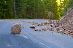 Landslide Blocked Road. This national forest road is blocked by a land slide of rock and debris to where it is a hazard for drivers in cars Royalty Free Stock Image