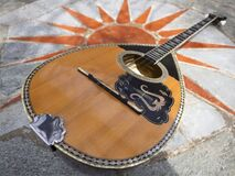 The national Greek stringed plucked musical instrument Bouzouki lies on a marble table in Greece
