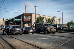 National guard armored swat tank and police officers barricading entrance to black lives matter protestors in minneapolis riots