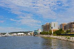 National Harbor waterfront panorama on a sunny morning. OXON HILL, MARYLAND, USA – SEPTEMBER 11 2016: National Harbor waterfront panorama with flags at half Stock Photography