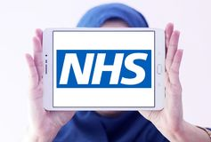 National Health Service , NHS , logo. Logo of National Health Service , NHS , on samsung tablet holded by arab muslim woman. The National Health Service NHS is Royalty Free Stock Image