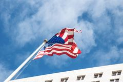 National pride. The US flag against the background of the blue sky and the City Hall Los Angeles. National honor and pride. The US national flag against the stock photography