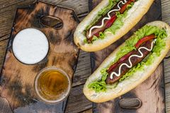 National Hot Dog Day, Traditional American, hot dogs, beer, Top view, copy space. National Hot Dog Day.Traditional American hot dogs and beer on a wooden surface stock photography