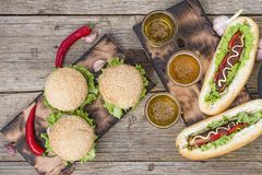 National Hot Dog Day, Traditional American, hot dogs, beer, Top view, copy space. National Hot Dog Day.Traditional American hot dogs and beer on a wooden surface royalty free stock photo