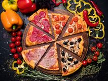 National italian meal pizza slice quattro stagioni. Traditional italian food cuisine. delicious pizza slice quattro stagioni with ham prosciutto tomatoes olives royalty free stock images