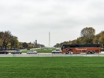 National mall in fall. Big bus tour trip cars beautiful fun love city life museums trees cloudy Washington DC District of Columbia Washington monument grass Stock Photography