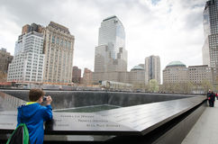 National 9/11 Memorial at Ground Zero. Boy takes photos at the North Pool of the National 9/11 Memorial at Ground Zero of the World Trade Center Royalty Free Stock Photos