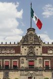 National Palace Facade Mexico City. Detail of the Palacio Nacional facade with a huge mexican, green, white and red striped flag Stock Photo
