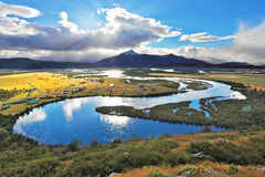 National Park Chile - Torres del Paine. River Valley Serrano. The smooth curves of the river, sparkling reflection of the sunset and clouds in blue water Royalty Free Stock Photography