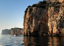 National park in Croatia. The yacht on calm sea near by rock. National park in Croatia Stock Photos