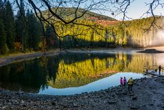 Tourists on Synevyr lake in autumn. National Park Synevyr, Ukraine - October 23, 2016: tourists on Synevyr lake in autumn. high altitude mountain lake among Stock Image