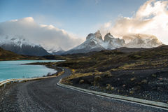 The National Park Torres del Paine, Patagonia, Chile. Beautiful road surrounded by a blue lake with the Paines in the background. The National Park Torres del Stock Image