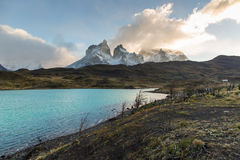 The National Park Torres del Paine, Patagonia, Chile. Beautiful road surrounded by a blue lake with the Paines in the background. The National Park Torres del Stock Images