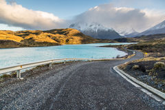 The National Park Torres del Paine, Patagonia, Chile. Beautiful road surrounded by a blue lake with the Paines in the background. The National Park Torres del Royalty Free Stock Photo