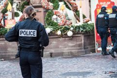 National policewoman patrolling in the pedestrian street at the christmas market with municipal police on background. Mulhouse - France - 9 December 2018 stock photography