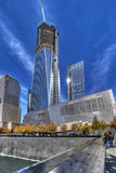National September 11 Memorial. A view of the National September 11 Memorial with the Freedom Tower being built at the World Trade Center site in New York City Stock Image