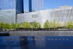 The National September 11 Memorial Museum. View of the 9/11 memorial museum, across the memorial inscription wall and the waterfalls in the footprint of one of stock photos