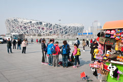 National Stadium. Beijing, China - April 2nd, 2013: Tourists stands next to souvenir kiosk near National Stadium in Chaoyang District, commonly known as Bird's Stock Images