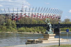 National Stadium and Statue of Mermaid in Warsaw, Poland. Statue of Mermaid, symbol of Warsaw on the Vistula Riverbank with National Stadium in the background in Stock Images