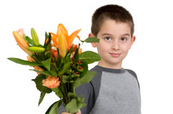National Teacher Appreciation Day. Eight years old boy presenting flowers to someone, perhaps its National Teacher Appreciation Day Stock Photo