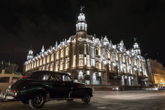 The National Theatre in Havana at night, Cuba. A classic american car passing by the National Theatre in Havana in Cuba, at night royalty free stock photography