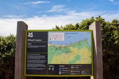 National Trust sign. Of Stamps and wheel engine house ruins Wheal Coates mine on cliffs near St. Agnes, Cornwall, UK stock photography