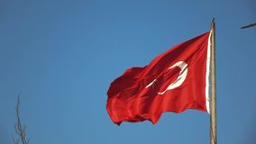 Turkish flag fluttering in the wind in the blue sky. National symbol of the state Turkey. Slow motion, Full HD video. National turkish Flag waving in the wind on stock footage