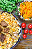 National Uzbek dish pilaf with meat, garlic and red pepper on a traditional plate, tomatoes, carrots and herbs Stock Photography