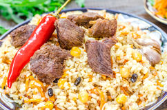 National Uzbek dish pilaf with meat and red pepper Stock Photo