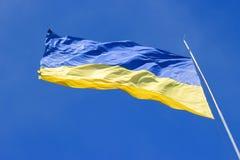 The national yellow-blue flag of Ukraine waving on the wind, against clear blue sky. Ukrainian symbol Stock Photos
