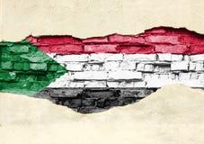 Nationale vlag van de Soedan op een baksteenachtergrond Bakstenen muur met gedeeltelijk vernietigde pleister, achtergrond of text stock illustratie