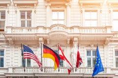 Nationale vlaggen op oude de bouwvoorgevel in Europese stad Vlaggen van de V.S., Duitsland, Oostenrijk, Europese Unie en gevouwen stock foto