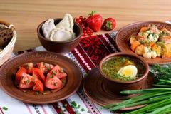 Nationales ukrainisches Abendessen: Gemüsesuppe mit Ei, Salat, vareniki mit Beeren, Ragout mit Tischdecke auf einem Holztisch Stockfotos