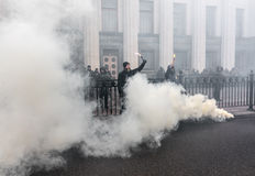 Nationalist groups burn flares during March of Dignity in Kiev. KIEV, UKRAINE - Feb 22, 2017: Activists of nationalist groups burn flares outside the building of Royalty Free Stock Photo