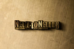 NATIONALLY - close-up of grungy vintage typeset word on metal backdrop Royalty Free Stock Photography