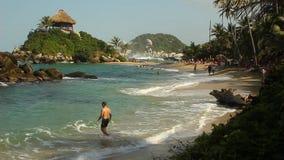 NATIONALPARK TAYRONA, KOLUMBIEN - Leute genießen ihre Ferien am Sandstrand von Cabo San Juan de GuÃa stock footage
