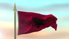Nationsflagga av Albanien som vinkar i vinden mot öglan för ultrarapid för solnedgånghimmelbakgrund den sömlösa