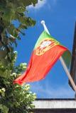 Nationsflaggan av Portugal framkallar i vinden mot en blå himmel arkivbilder