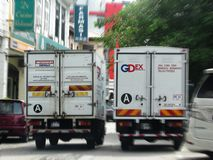 Nationwide Express And GDExpress Vans Side By Side - Motion Blurred. Two leading Malaysian courier delivery companies, Nationwide Express and GDExpress/GDEx, and Royalty Free Stock Image