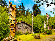 Native American Clan House and Totems. Ketchikan, AK, USA - May 24, 2016: Native American Totems and Clan Houses located at Totem Bight State Historic Site royalty free stock photography